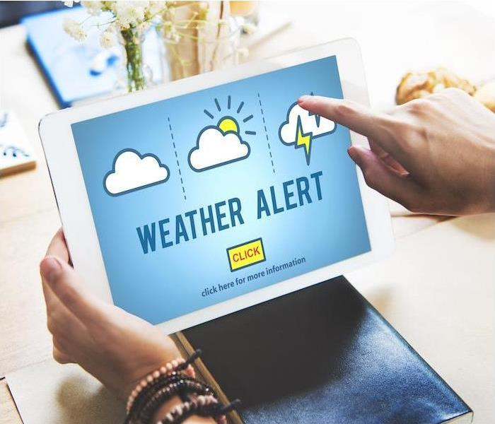person on a tablet using weather alert app